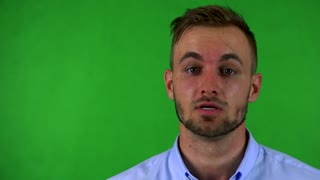 young handsome business man talks to camera - green screen - studio - closeup