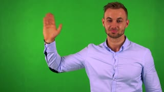 young handsome business man waves with hand - green screen - studio