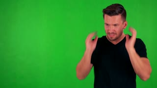 young handsome caucasian man is afraid (man covers his ears with hands) - green screen - studio