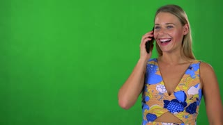 young pretty blond woman phones with smartphone - green screen - studio