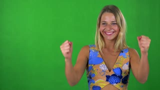 young pretty blond woman rejoices - green screen - studio