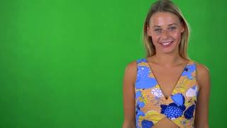 young pretty blond woman talks to camera - green screen - studio