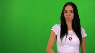 young pretty woman points to camera with finger - green screen - studio