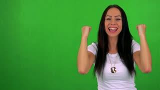 young pretty woman rejoices - green screen - studio