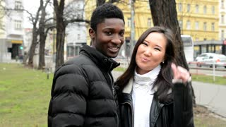 Happy couple show thumb on agreement - black man and asian woman - urban street