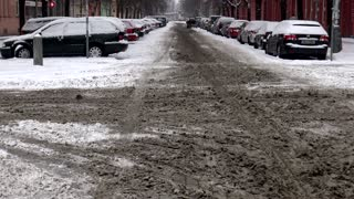 Snowy crossroad with dirty drift of snow in town