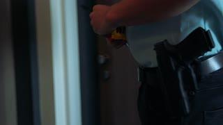 A police officer puts a crime scene tape across an apartment door - closeup
