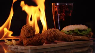 Hamburger and chicken fast food on fire slow motion background.
