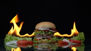 Hamburger fast food on fire slow motion background.