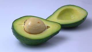 water splashing on a avocado fruit in slow motion.