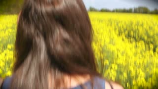 A woman walks through a field of yellow flowers on a sunny day
