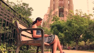 BARCELONA, SPAIN - SEPTEMBER 2013: Woman sits on bench by the Sagrada Família church in Barcelona, reading a guide book
