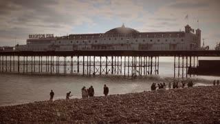 BRIGHTON, UK - APRIL 2015: Tourists on Brighton beach near the pier