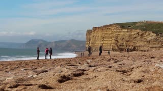 BURTON BRADSTOCK, UK - APRIL 12, 2016: Tourists walk on a pebble beach with cliffs in background