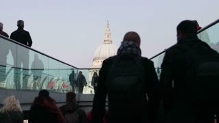 Commuters and tourists at the start of the Millennium Bridge with St Paul's Cathedral in background (mid shot)