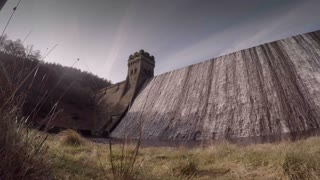 DERBYSHIRE, UK - MARCH 14, 2016: Water flows over the edge of the Derwent Dam, site of the Dam Busters training missions.