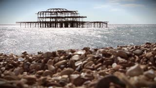 Derelict pier at Brighton with pebble beach