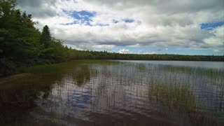 Drone POV flying over scenic Canadian lake