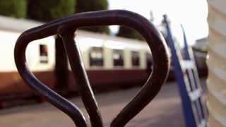 Focus on luggage trolley handle in foreground with blurred railway station staff and vintage carriage in background