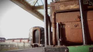 Focus on vintage luggage in foreground as blurred steam train pulls into the station in background.