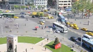 ISTANBUL, TURKEY - MAY 10, 2010: Morning rush hour in Taksim Square with people, buses and yellow taxis