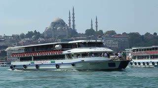 ISTANBUL, TURKEY - SEPTEMBER, 2009: A ferry crosses the Golden Horn with mosques visible on the far shore
