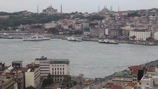ISTANBUL, TURKEY - SEPTEMBER, 2009: Galata bridge crosses the Bosphorus river at the Golden Horn, with boats and mosques visible in the distant shoreline