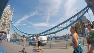 LONDON, UK - JULY 2015 Panning time lapse clip of tourists and vehicles crossing Tower Bridge. Camera pans to the Tower of London