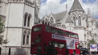 LONDON, UK - AUGUST 4, 2016:  Open topped tourist buses passes the Royal Courts of Justice