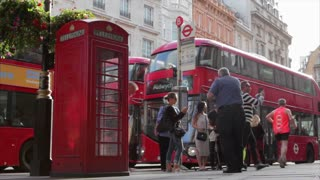 LONDON, UK - AUGUST 4, 2016: Red bus arrives and passngers disembark near traditional red phone booth near Trafalgar Square