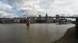 LONDON, UK - AUGUST 4, 2016: Timelapse ferry boats pass the Millennium Bridge and St Pauls Cathedral