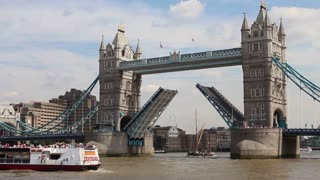 LONDON, UK - AUGUST 8, 2013: Tower bridge with open drawbridge as tall ship sails through gap