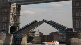 LONDON, UK - AUGUST 8, 2013: Tower Bridge's drawbridge closes as a catamaran ferry floats under it