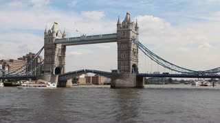 LONDON, UK - AUGUST 8, 2013: Tower bridge's drawbridge finishes closing after a catamaran ferry passes