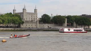 LONDON, UK - AUGUST 8, 2013: Tower of London and Thames, with passing boats