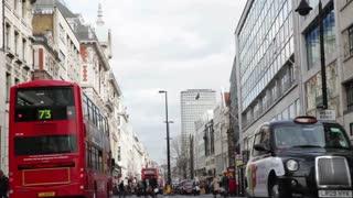 LONDON, UK - FEB, 2012: Pedestrians cross between busy traffic on Oxford Street