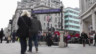 LONDON, UK - FEB, 2012: Pedestrians pass Oxford Street Tube Station