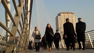 LONDON, UK - FEBRUARY 19, 2013: Tourists and commuters cross the Hungerford Bridge over the Thames