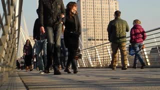 LONDON, UK - FEBRUARY 19, 2013: Tourists and commuters crossing the Hungerford Bridge over the Thames