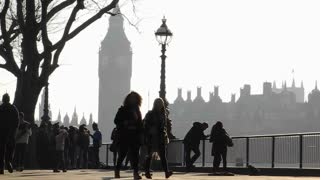 LONDON, UK - FEBRUARY 19, 2013: Tourists walk along the Southbank of the river Thames with Big Ben in the background