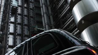 LONDON, UK - JAN 28 2016: Elevators going up and down the exterior of the Lloyds of London building, with foreground taxi