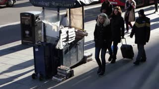 LONDON, UK - JAN 28 2016: Pedestrians pass newspaper vendor on Bishopsgate