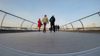 LONDON, UK - JANUARY 23, 2015: Low angle time-lapse of commuters and tourists crossing the Millennium Bridge