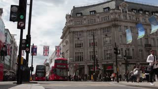 LONDON, UK - JUNE 28, 2016:  Buses and Taxis pass under British flags at Oxford Circus