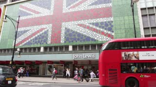LONDON, UK - JUNE 28, 2016:  Iconic London buses and taxis pass giant British flag on John Lewis store in Oxford Street