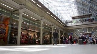 LONDON, UK - JUNE 28, 2016: People walk past shops in St Pancras International railway station