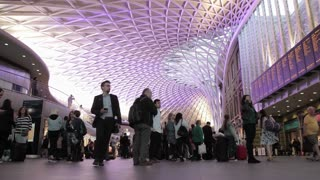LONDON, UK - JUNE 28: Shoppers and commuters watch Departure boards at Kings Cross Station
