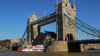 LONDON, UK - MARCH 25, 2016: A paddle steamer passes through Tower Bridge with its drawbridge raised