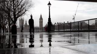 LONDON, UK - MARCH 6, 2016: People and landmarks reflected in rain puddles on the Southbank of the Thames