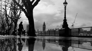 LONDON, UK - MARCH 6, 2016: People, trees and Big Ben reflected in puddles on the Southbank